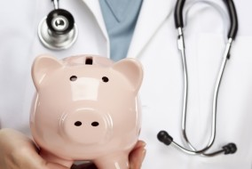 Female Doctor with Stethoscope Holding Piggy Bank Abstract.